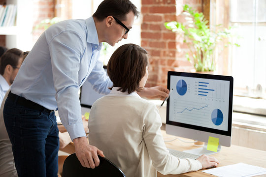 Executive manager helping employee preparing online statistical report in office