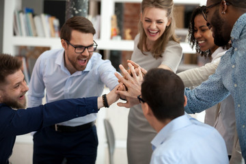 Excited motivated multi-ethnic team people give high five in office