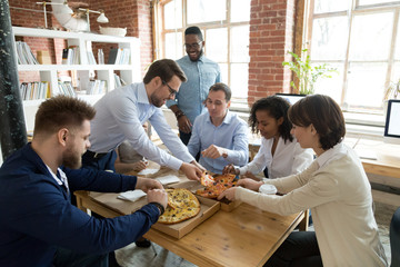 Happy diverse staff people sharing pizza at break in office