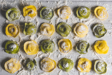 Homemade fresh Italian ravioli pasta on white wood table  background,top view.