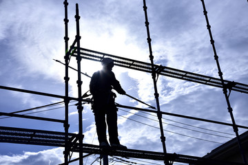 """A building worker """"steeplejack"""" assembling the scaffold at the housing construction site : Framework construction"""