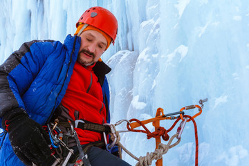 ice climber with a serious face on the wall of a glacier