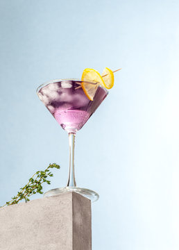 Cold cocktail with lavender syrup and lemon with ice on a light blue background.