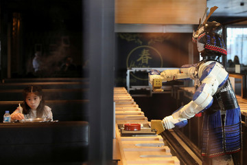 A robot waitress brings food to a table at the Hajime Robot restaurant in Bangkok
