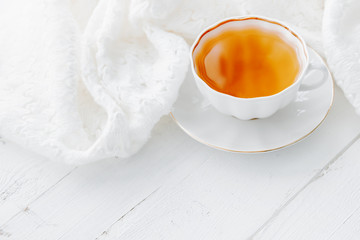 Tea in white cup with white knitted plaid. Hot morning tea drink on white background with copy space. High key image of tea