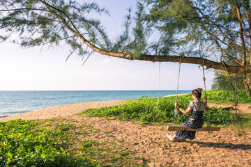 Happy young woman enjoying freedom sitting wooden swing hanging under the tree on the beach with beautiful tropical island