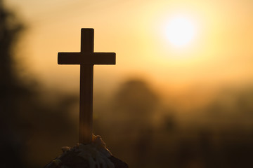 Christian wooden cross on a background with dramatic lighting,  Jesus Christ cross, Easter, resurrection concept. Christianity, Religion copyspace background.
