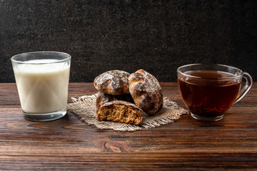 Traditional russian gingerbread with tea or milk on dark wooden background.