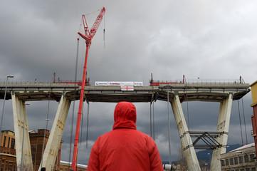 Person looks at the collapsed Morandi Bridge in Genoa