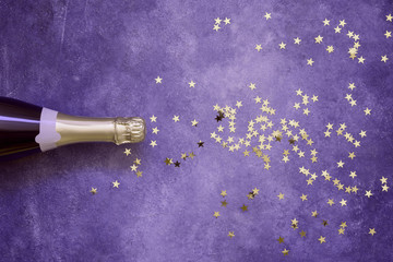 Champagne bottle and confetti stars on ultra violet background. Copy space,top view. Flat lay