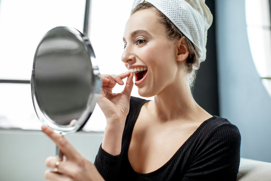 Woman wearing plastic form for teeth at home