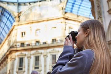 Tourist girl taking a photo in Galleria Vittorio Emanuele II in Milan Italy