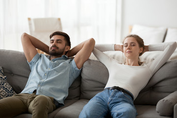Calm lazy couple relaxing on comfortable sofa resting together