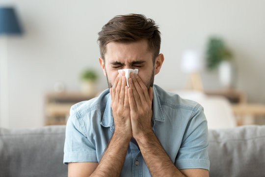 Ill young man sneezing in handkerchief blowing wiping running nose