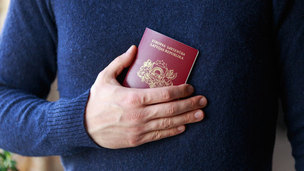 man holding latvian, european union passports. Devon, United Kingdom, January, 2019