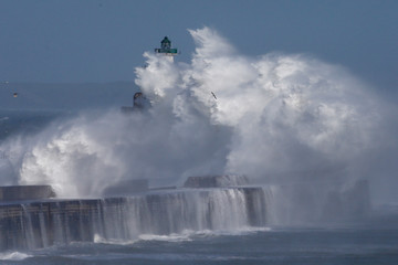 Waves crash against a lighthouse during a windy day in Boulogne-sur-Mer