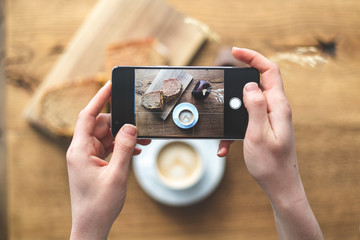 Woman making photo of her breakfast coffee and sandwich on cellular