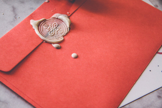 Paper pink envelope with sealing wax stamp and invitation card