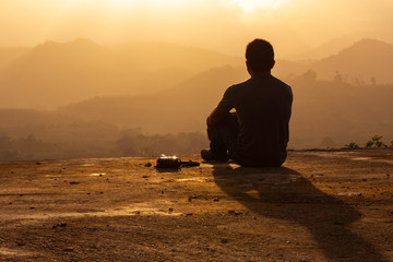 silhouette man sitting at sunrise and mountain background