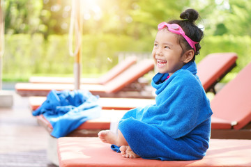 Asian child or kid girl laugh smiling with wet cold and sit on bed or pool chair with blanket towel on swimming pool with happy in water park for refreshing relax or exercise on summer holiday travel
