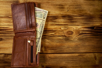 Opened wallet with american dollars on wooden table. Top view