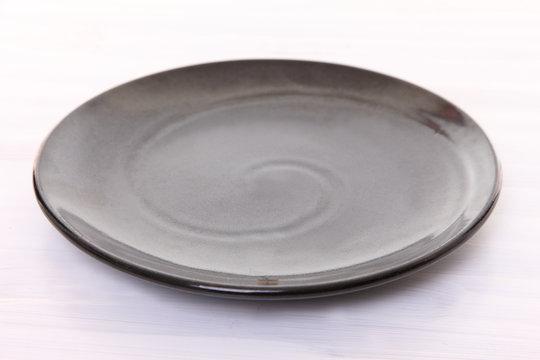 白い木製テーブルに置かれた黒い皿