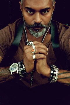 Portrait of an attractive stylish man with a beard and tattoos looking on straight and holding hands together with different jewelries - Image