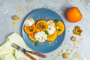 Sliced persimmon with yogurt, brown sugar, pine nuts and fresh mint