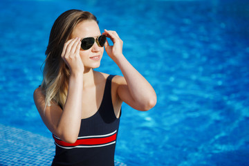Woman wearing sunglasses with long beautiful legs and hair sits on the edge of a pool with blue water.