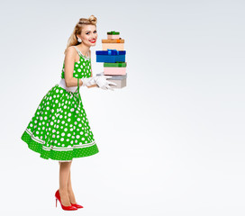 Full body of woman in pin-up style dress with gift boxes