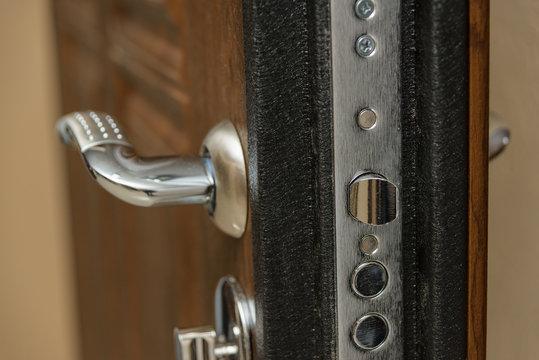 Wooden door. Internal lock design. Keyhole. Metal door handle. Anti-burglar armored door. Metal interior doors. The design of the door. Peephole.