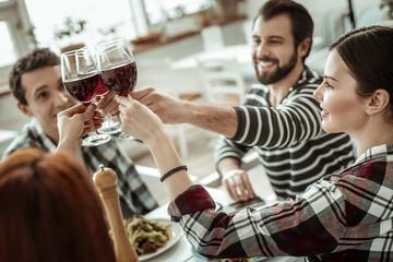 Joyful people sitting together around big table