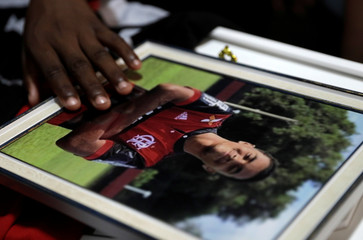 A hand is seen over a picture of soccer player Vinicius de Barros Silva Freitas during his funeral service after a deadly fire at Flamengo soccer club's training center, in Volta Redonda
