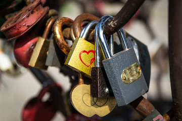 Heart-shaped locks hang on the iron fence. Valentine's Day background.