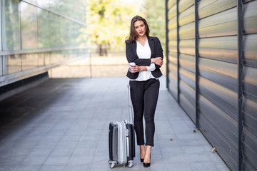 Business woman with suitcase and coffee to go waiting for transport