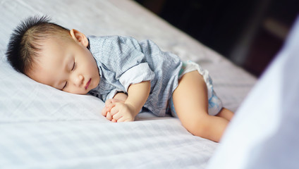 Toddler kid sleeping peacefully on white bed