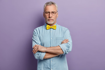Horizontal shot of attractive woman with serious expression, looks directly at camera, keeps arms folded, wears yellow bowtie and denim shirt, isolated over purple background. Aging concept.