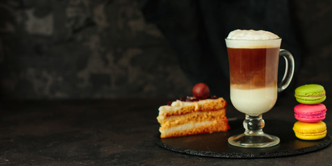 Latte in a transparent cup, macaroon cake (coffee dessert). Top Food background