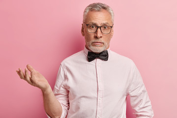 Indoor shot of puzzled mature man with thick grey stubble, wears spectacles, dressed in elegant shirt with black bowtie, gestures in hesitation, poses over rosy background. Doubtful grandfather