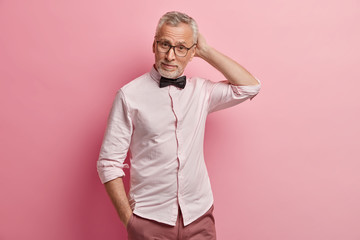 Waist up shot of attractive bearded grey haired man pensioner scratches head, holds hand in pocket, wears stylish elegant clothes, poses over pink background, has puzzled expression. Let me think