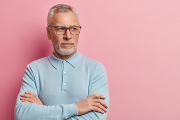 Mature bearded serious man keeps hands crossed, focused aside, wears transparent glasses and blue jumper, contemplates about something, isolated over pink background with empty space for your text