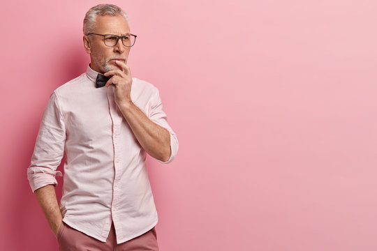 Pensive mature wrinkled man holds chin, lost in thoughts, looks away, keeps hand in pocket, dressed in formal clothes, models over rosy background with empty space for your promotional content