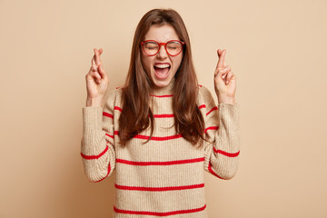 Excited satisfied lady has hopeful expression crosses fingers as prays for something desirable, dreams about something keeps mouth widely opened stands faithful over beige background dressed in jumper