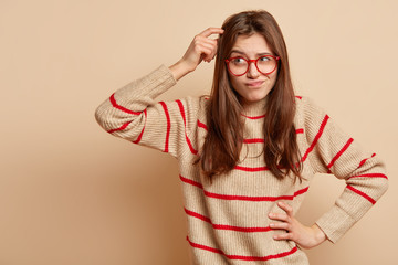 Indoor shot of puzzled of European woman scratches head, keeps hand on waist, dressed in loose sweater, tries to recollect something in mind, isolated over brown background with blank space.