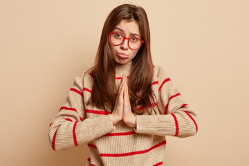 Regretful brunette woman keeps palms pressed together, feels guilty, beggs for forgiveness, has desperate facial expression, wears transparent glasses and sweater, isolated over beige studio wall