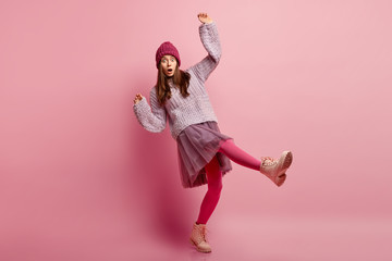 Photo of surprised frightened young woman falls down, stands on one leg, wears headgear, jumper, skirt, pink pantyhose and boots, isolated over rosy background. Horizontal shot. Fear concept
