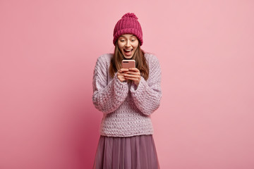 Photo of pleased European young woman with happy facial expression, holds mobile phone, recieves congratulation in message, wears stylish skirt and loose jumper, isolated over pink background