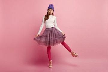 Studio shot of amazed pretty young woman demonstrates her new stylish skirt, wears bright pink tights, raises leg, wears boots, models over rosy background, has eyes popped out, appealing look