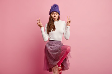 Image of surprised European woman with bugged eyes, widely opened mouth, raises knee, makes peace sign with both hands, wears hat, white turtleneck sweater and skirt, astonished by something