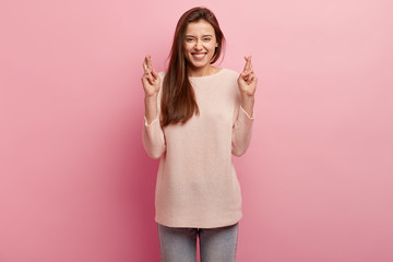 Dreamy tender woman with positive smile, keeps hands raised, crosses fingers, asks for favour, dressed in casual jumper, isolated over rosy studio wall, believes in good luck. May dreams come true